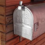 silver mail box beside wall